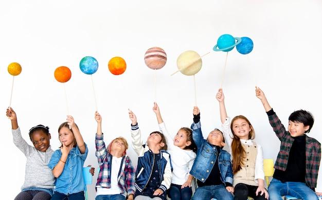 白い背景にペーパークラフトの銀河のシンボルを保持している子供のグループ