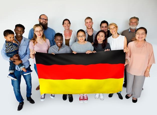 国旗を保持し、写真撮影のためにポーズを取るグループの人々