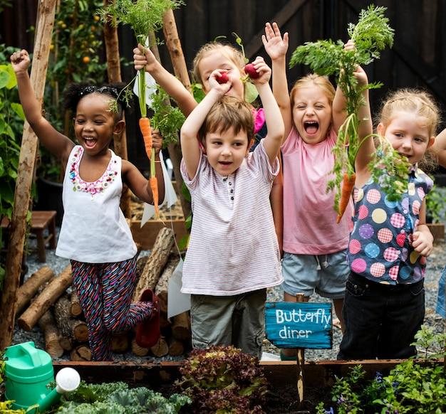 ガーデニングアウトドアを学ぶ幼稚園の子供のグループ