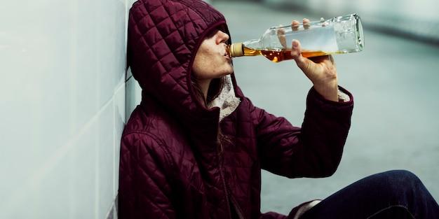 Бездомный алкогольный алкогольный напиток, сидящий на полу