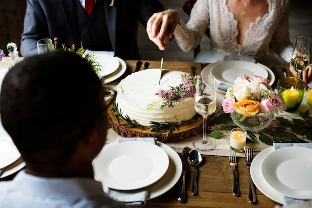 結婚式のレセプションでケーキを切る花嫁と花婿