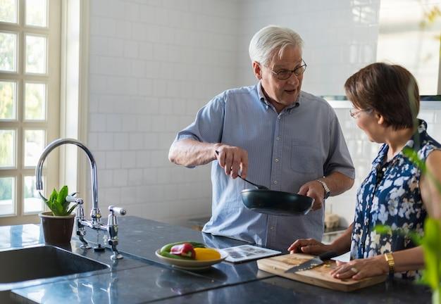 一緒に料理する高齢者カップル