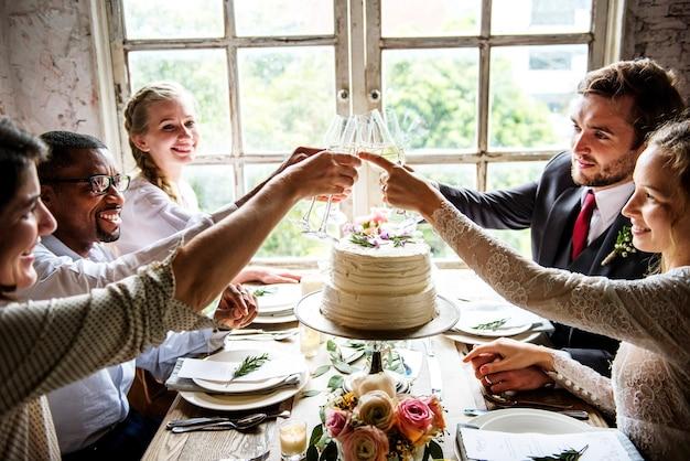花嫁と花婿の結婚式のレセプションで人々を抱きしめているワイングラス