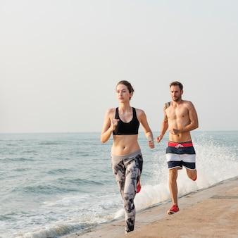 ビーチで走っている健康的な若いカップル