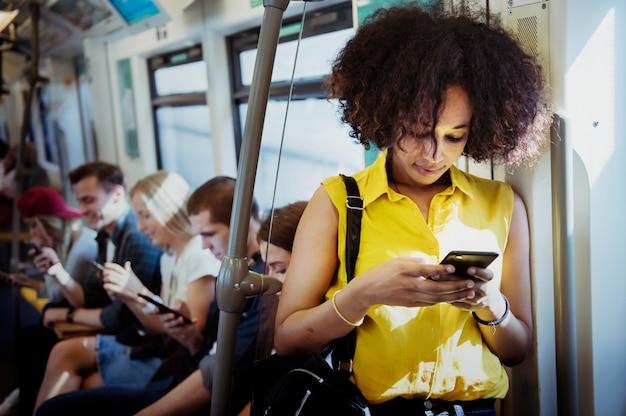 地下鉄でスマートフォンを使っている若い女性