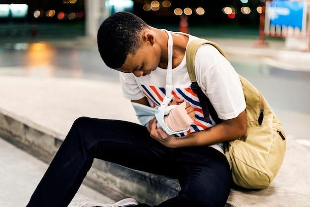 腕をサポートしている負傷した若い男