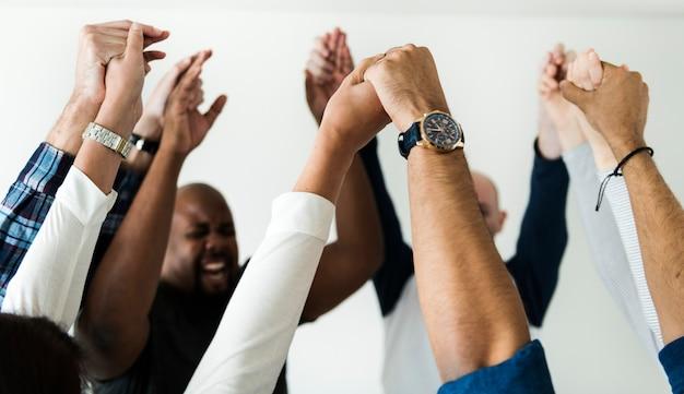 多様な人々が手を結び合う成功と祝賀コンセプト