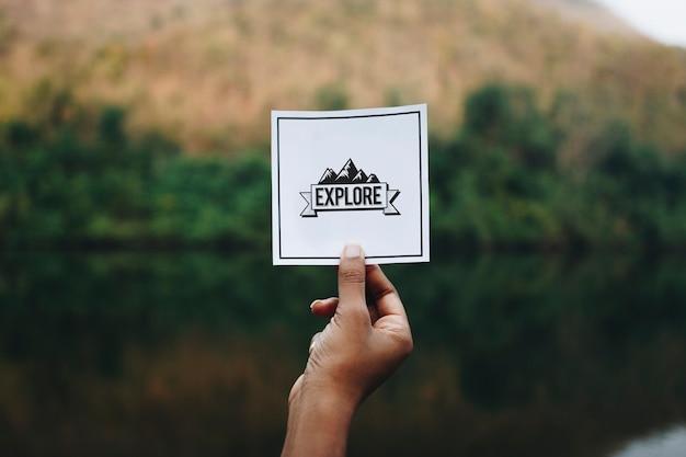自然のモックアップでメモを保持している旅行者
