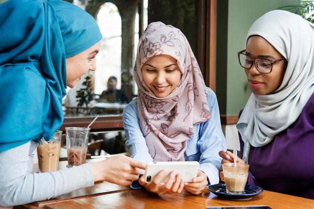 スマートフォンを見ているイスラム女性のグループ