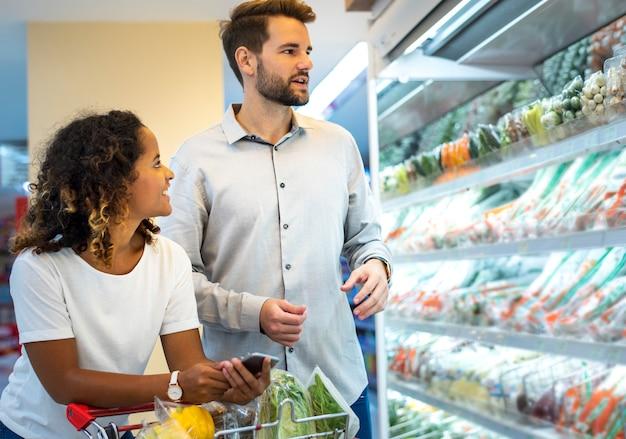 スーパーマーケットで一緒に買い物をするカップル