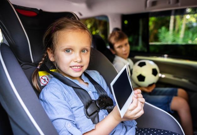車の中でデジタル機器を持っている姉妹と兄弟