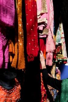 市場でカラフルなサリーを選ぶ女性
