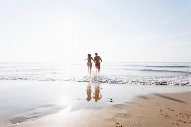 浜辺で走っている陽気なカップル