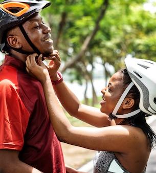 女性は彼女のボーイフレンドのために自転車のヘルメットを締める