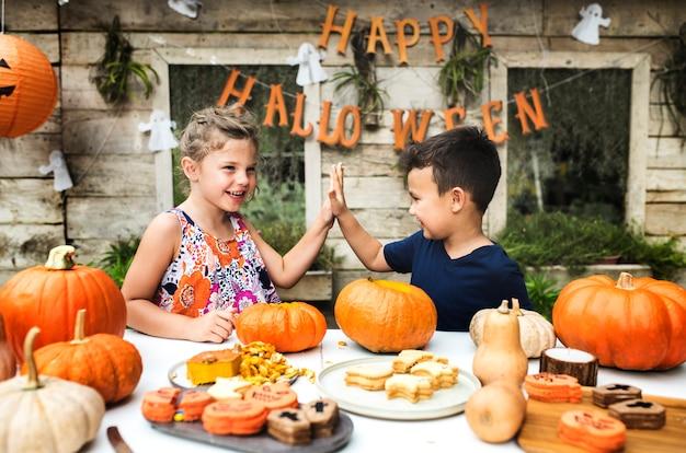 Маленькие дети, вырезающие хэллоуин-джец-о-фонари