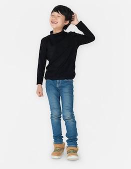 Азиатский мальчик смеется, почесывая голову