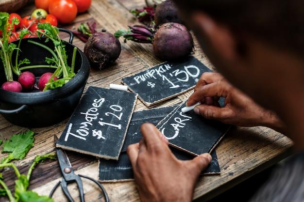 チョークボード上の野菜価格を書く男のリアビュー