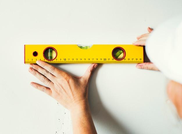修理士は、壁に定規を測定する作業