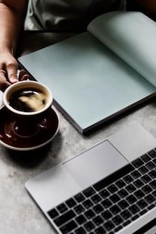 雑誌を読んでいる間にコーヒーを飲む女性