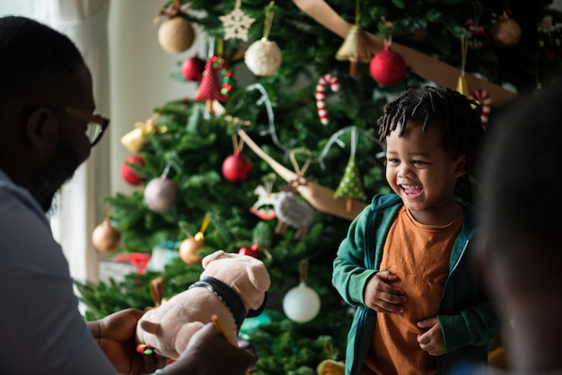 小さな子供がクリスマスプレゼントを受け取っています