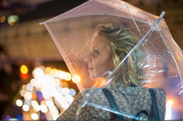 彼女の傘の下にカバーを取っているブロンドの女性