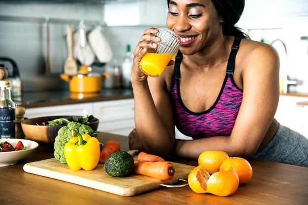黒の女性は、オレンジジュースを飲んでいる
