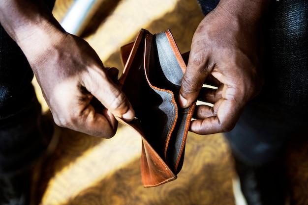 彼の空の財布をチェックしている男
