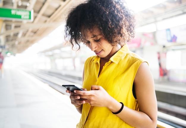 地下鉄の駅でスマートフォンを使用している若い女性