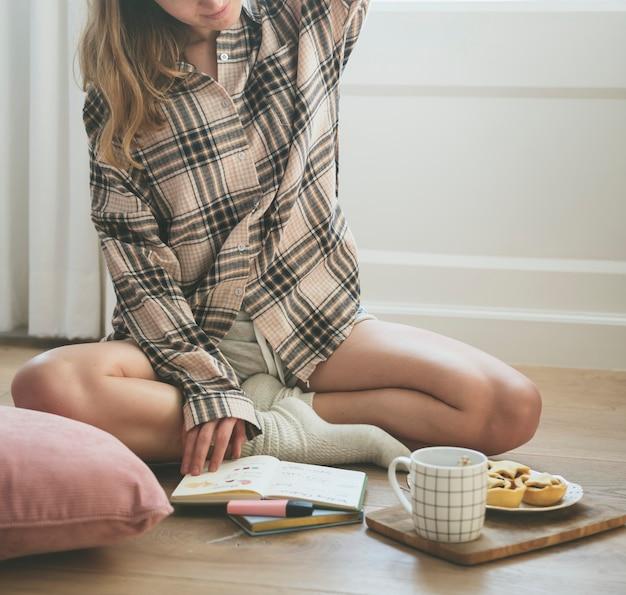 床で勉強している白人の女の子
