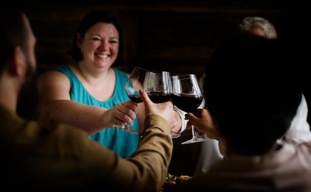 Счастливые люди приветствуют красное вино
