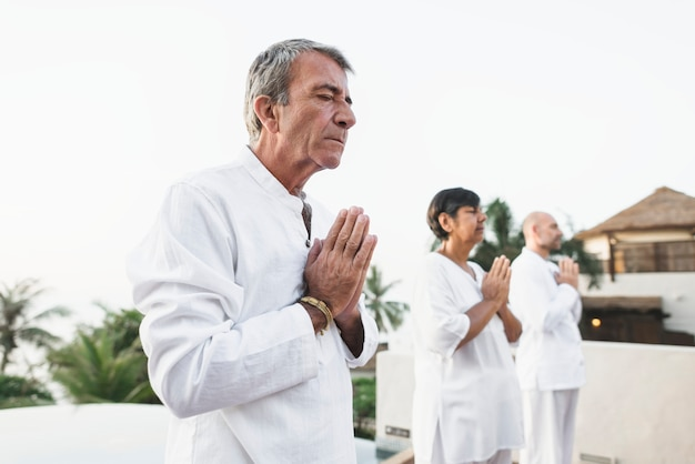 Группа пожилых людей, практикующих йогу
