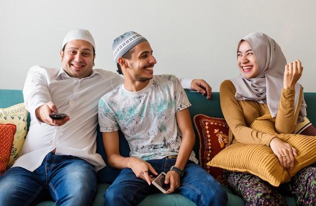 家でテレビを見ているイスラム教徒の家族
