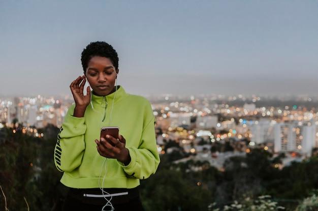 電話から音楽を聴く女性