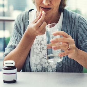 高齢の女性が薬を服用する
