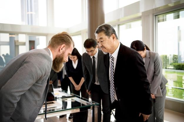 ビジネスマンに弓矢で敬意を表している日本人ビジネスマン