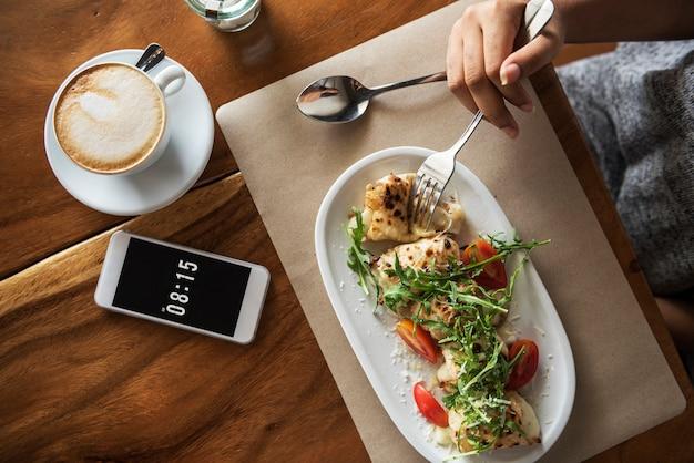 アフリカ系アメリカ人の女性は、カフェで食べ物を食べている
