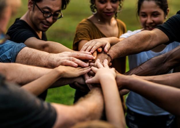 多様な人々のグループがスタックサポートを一緒に手渡す