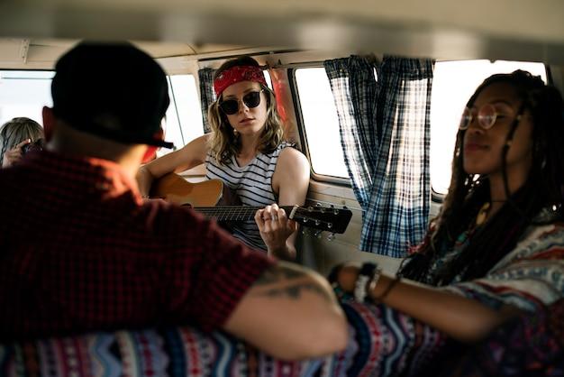 一緒に友達と一緒にロードトリップでギターを演奏する女性