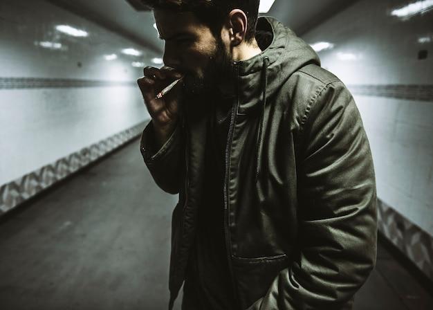 Бездомный человек, курящий зависимость от сигарет