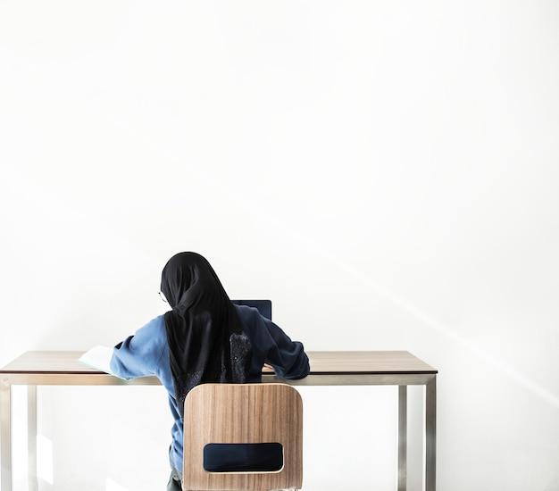 ラップトップで勉強しているイスラムの女の子