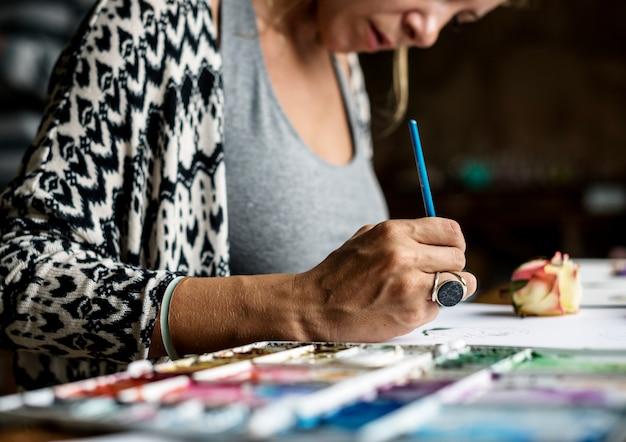 バラの水彩画をやっている女性