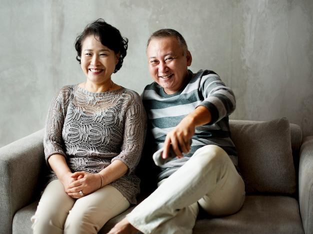 一緒にソファに座っているアジアのシニアカップル