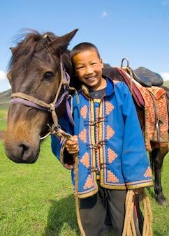 彼の馬に頭を傾け、屋外で笑っている少年。