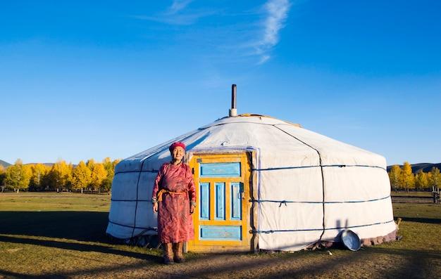 モンゴルの女性がテントの前に立っている
