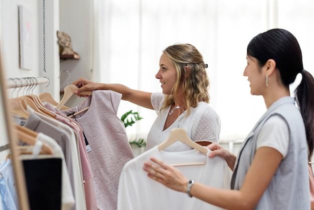 顧客はラックで服を選んでいます