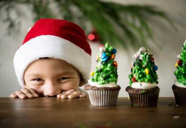 クリスマスツリーの朗らかな少年はカップケーキを飾った