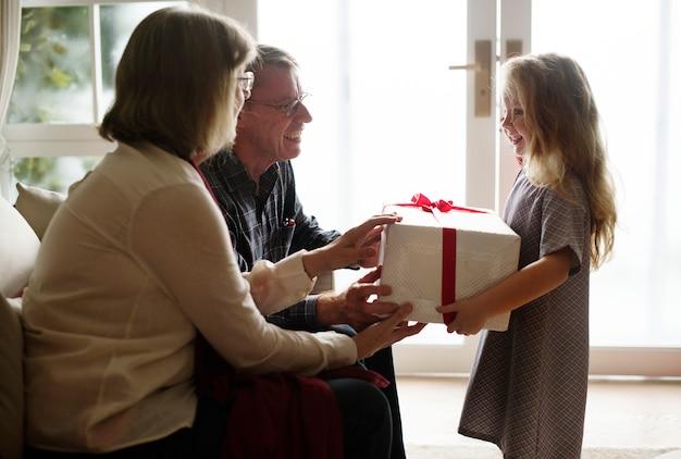 彼女の両親からクリスマスプレゼントを受けている少女
