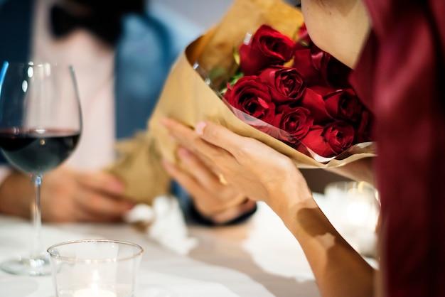 赤いバラ花束を与える男