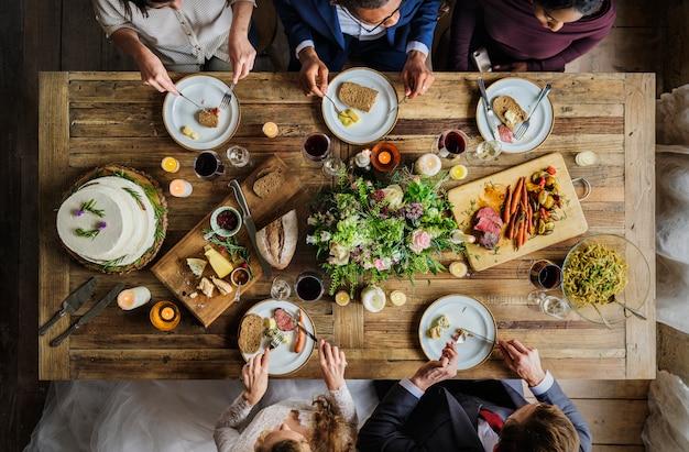 結婚式のレセプションで友達と食事をする新郎新婦