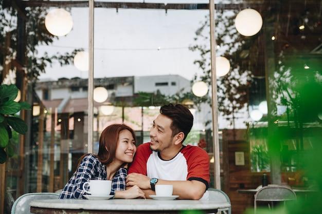 コーヒーを持っている素敵なアジア人カップル